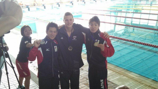 Matthew Klotz (center), posing here with his fellow medalists in the 100 backstroke.