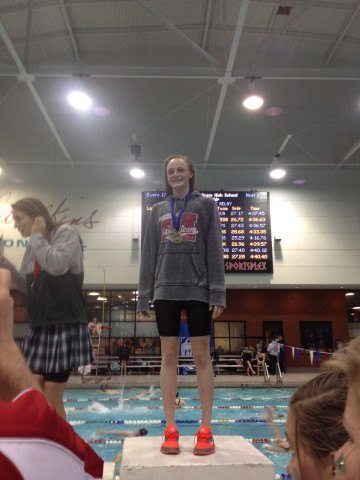 Logan Graumann accepts her gold medal in the 100 free at the 2014 Tennessee High School State Championship meet. Courtesy: Tom Graumann