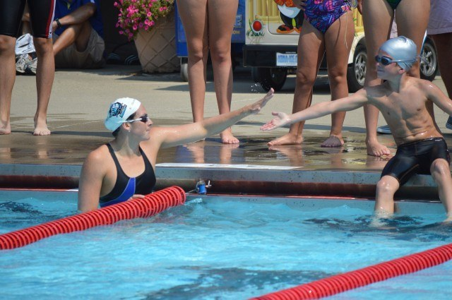 Lacey Nymeyer gives a participant a high five after a race from the blocks
