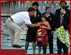 Coach Peter Solomon fastens Aliana's Team IMPACT pin to her new team suit.