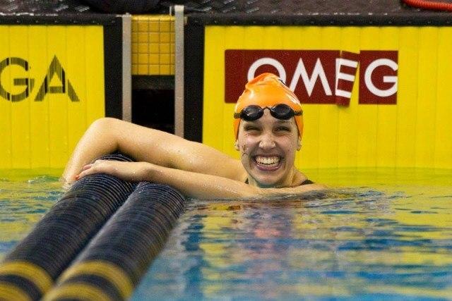 Virginia's Courtney Bartholomew wins the 100 backstroke. Courtesy of Todd Kirkland, theACC.com