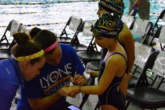 Coach Alison Credit writes event and heat numbers on her swimmer's arm, Sophie Zielinski of La Grange, as fellow swimmer, Grace Credit, looks on