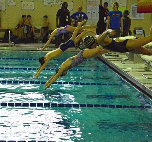 Katie Hess, 10 of La Grange, Ethan Baum, 10, Molly Norgle, and Emily Claesson, 10 all from Lyons Aquatics practice their starts off the block during warm-ups at Lyons Aquatics County Line Classic meet Feb 14.