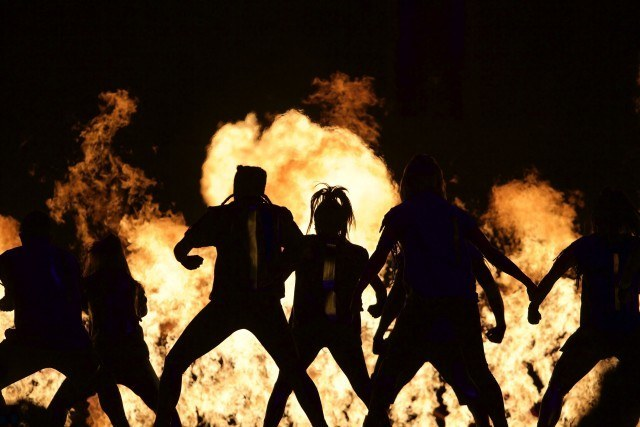 Toronto -- Cirque Du Soleil performers are silhouetted by fire while performing at the opening ceremonies of the 2015 Toronto  Pan Am games at the Pan Am Dome. July 10, 2015.