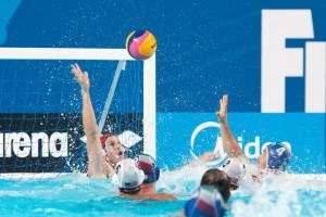 Peitro Figlioli of Italy lofts his teams fifth goal over the arms of U.S.A. goalie in preliminary round water polo competition at the 2015 FINA World Championship held in Kazan, Russia.